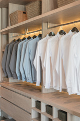 row of shirts hanging on rail