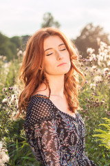 Young red-haired woman on a dirt summer meadow