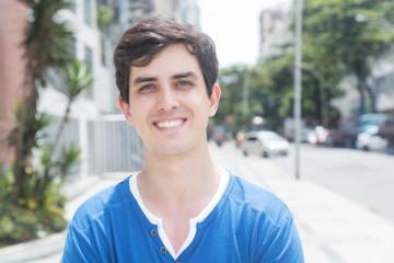 Moderner junger Mann im blauen Shirt in der Stadt