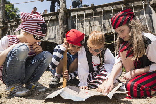 Girls examining a treasure map in a adventure playground, Bavaria, Germany