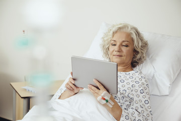 Senior woman in hospital using digital tablet
