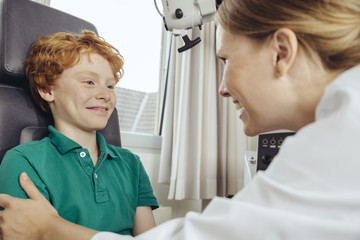 Female doctor talking to child patient in ENT practice