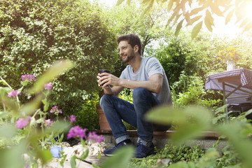 Smiling man sitting in garden with cup of coffee