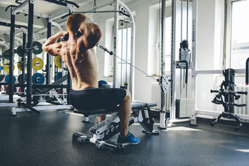 Physical athlete exercising with cable machine