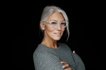 Portrait of smiling woman wearing glasses in front of black background