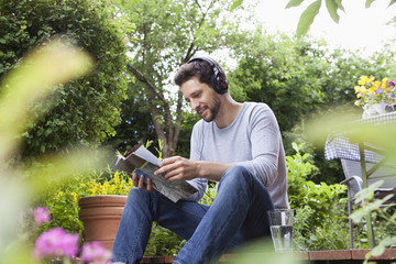 Relaxed man sitting in garden with headphones and magazine