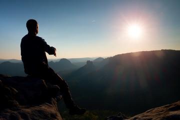 Man tourist sit finally on peak of mountain. Travel mountain scene. Sun at horizon