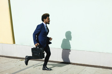 Young businessman with briefcase running on pavement