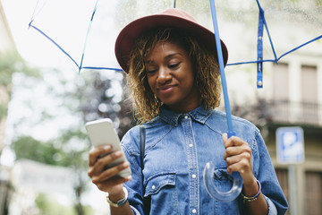 Spain, Barcelona, portrait of smiling young woman with umbrella and smartphone