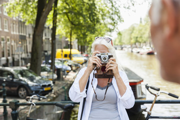Netherlands, Amsterdam, senior woman taking a picture with analog camera at town canal