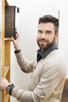 Man in office taking file folder from cabinet