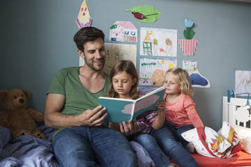 Father and his little daughters sitting together on bed in children's room reading a book