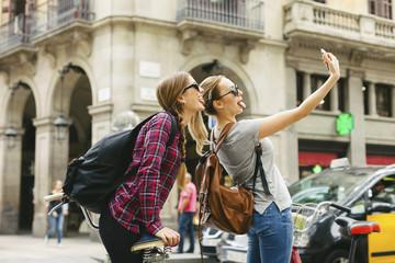 Spain, Barcelona, two playful young women taking a selfie