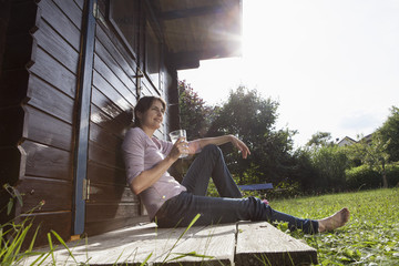 Smiling woman sitting at garden shed with glass of water