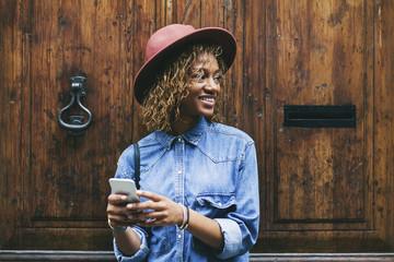 Spain, Barcelona, portrait of smiling young woman with smartphone  standing in front of wooden door