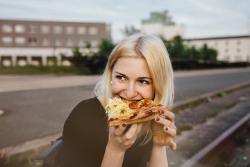 Close-up of a young woman eating pizza