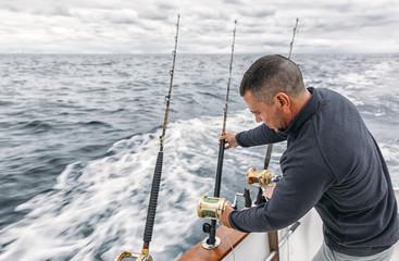 Spain, Asturias, Fisherman on fishing boat on Cantabrian Sea