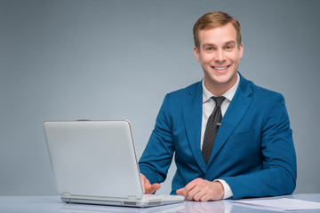 Smiling newsman working with his laptop.