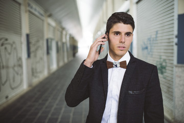 Young man on the phone wearing jacket and a wooden bow tie