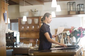 Waitress preparing bill at counter