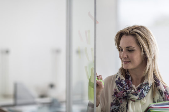 Woman in office writing on sticky notes