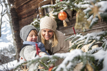 Austria,  mother and son looking at decorated Christmas tree in front of farmhouse