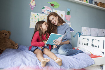 Mother and little daughter sitting together on bed in children's room with a book
