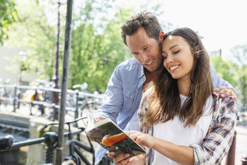 Netherlands, Amsterdam, couple reading tourbook