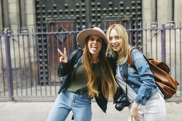 Spain, Barcelona, two playful young women in front of entrance portal