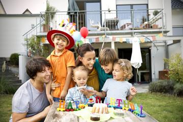 Happy family having a children's birthday party in garden