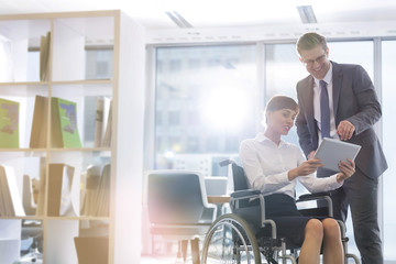 Businesswoman in wheelchair and businessman using digital tablet in office
