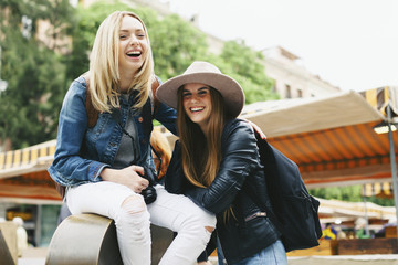 Spain, Barcelona, two happy young women in the city