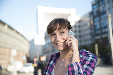 Germany, Berlin, portrait of young woman telephoning with smartphone