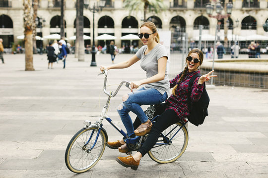 Spain, Barcelona, two happy young women sharing bicycle in the city