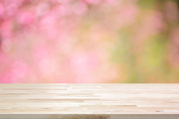 Wood table top on blurred background of pink cherry blossom flowers
