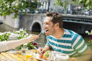Netherlands, Amsterdam, woman feeding man at outdoor restaurant at town canal