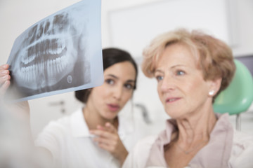 Dentist explaining x ray image to senior woman in dentist's chair