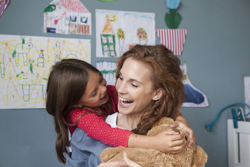Mother and little daughter having fun together in children's room