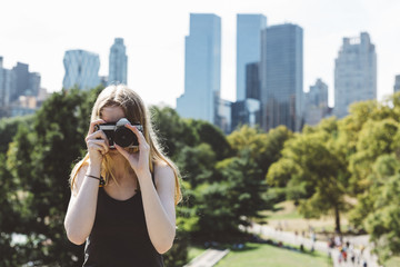 USA, New York City, young woman photographing in Central Park