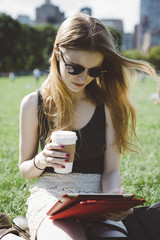 USA, New York City, young woman using digital tablet in Central Park