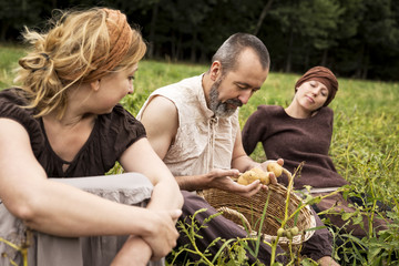 Three people sitting on field with potatoes in wicker basket