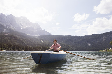 Germany, Bavaria, Eibsee, man in rowing boat on the lake