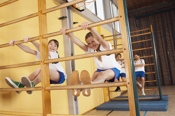 Germany, Emmering, Girls (12 14) climbing wall bars with boys in background