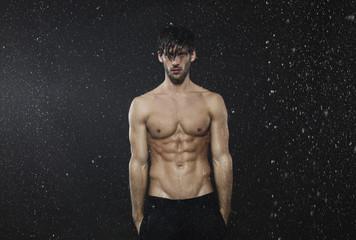 Man standing in rain, hands in pocket.