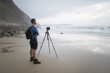 Spain, Valdovino, photographer standing on the beach taking photos with a tripod