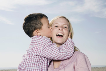Germany, Schleswig Holstein, Amrum, Son (3 4) kissing mother, laughing, portrait