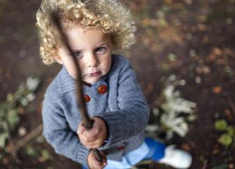Portrait of little boy holding a stick
