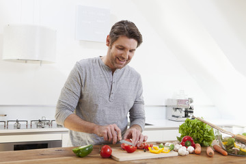 Germany, Bavaria, Munich, Man chopping vegetables in kitchen