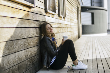 Smiling woman with coffee to go sitting on ground leaning against wooden wall