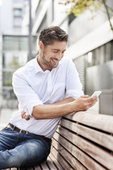 Portrait of smiling man sitting on wooden bench while looking at his smartphone